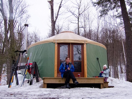 lady sitting outside camping tent during winter