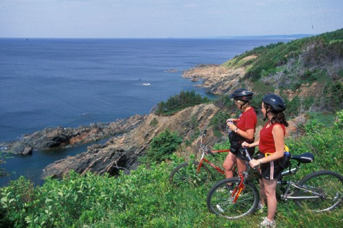 Two women looking at the sea with their mountain bike