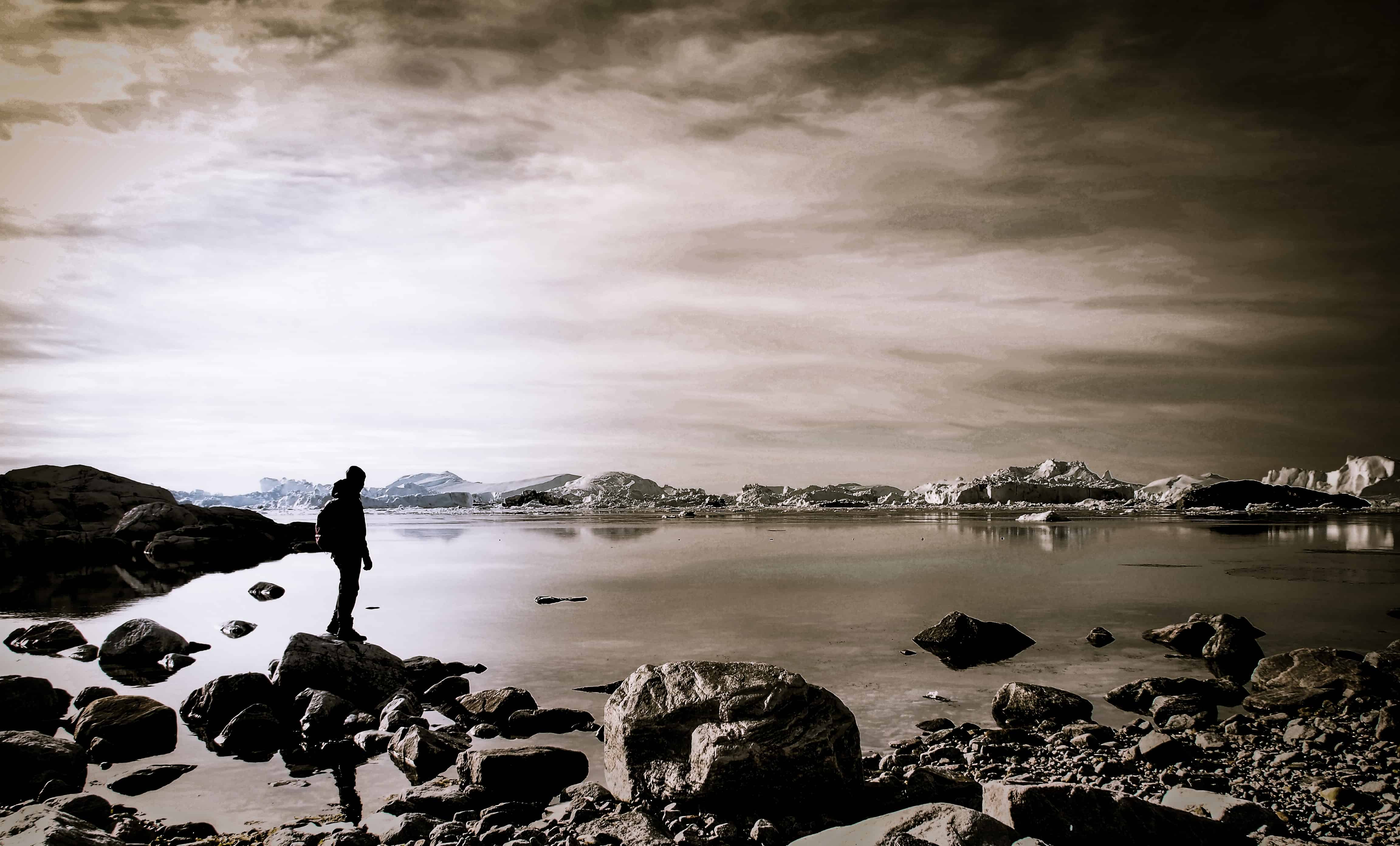 Image result for sea1000 × 604 person standing on rock near body of water