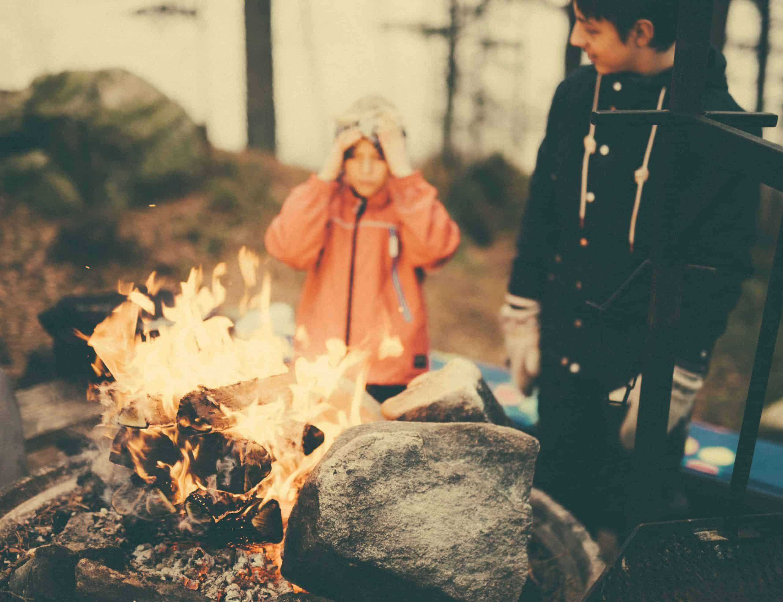 a child and teenager stand near a fire in bors